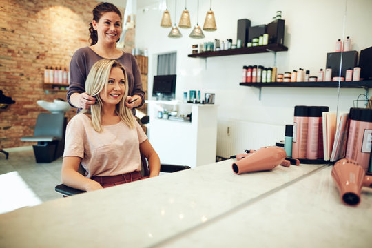 Smiling woman looking at her stylist in a salon mirror