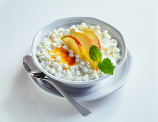 Granular cottage cheese with pear wedges and honey in a bowl