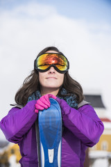 Woman with skis and ski goggles