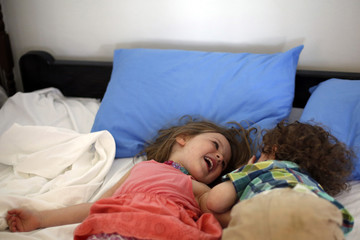 Sister and brother playing in bed