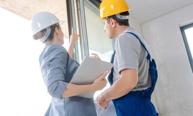 Architekt und Arbeiter auf Baustelle überprüfen die Fenster im Rohbau