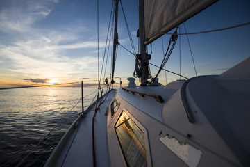 Sailing at sunset. A view from the yacht's deck to the bow and sails, Baltic sea, Latvia