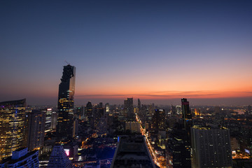 Scenic view of MahaNakhon and many other lit skyscrapers in downtown Bangkok, Thailand, from above in the evening. Copy space.
