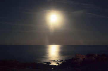 Looks like the sun but it's a long exposure of the moon over rocky cliffs and the sea.