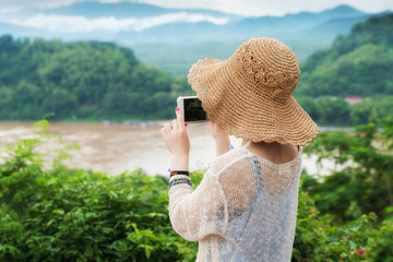 Asian young girl with hat on use cellphone or mobile phone take photo of greenery view of beautiful forest and river in laos
