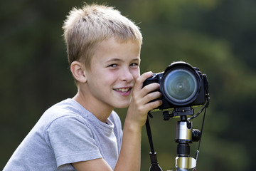 Young cute blond child boy taking picture with tripod camera on blurred green copy space background.