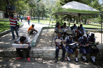 A boy selling pasties takes a nap as students read comics next to a Biblio Tap-Tap, a mobile library, in a park of Port-au-Prince