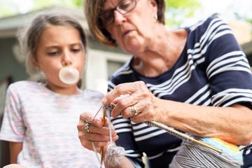 Grandmother teaching knitting to granddaughter