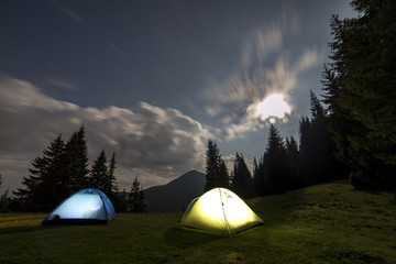 Bright big moon in dark blue cloudy sky over two tourist tents on green grassy forest clearing among tall pine trees on distant mountain background. Tourism, night camping in summer mountains.