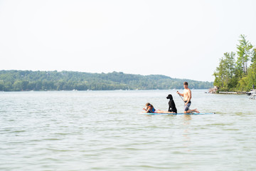 Father and daughter enjoying paddleboarding along with dog