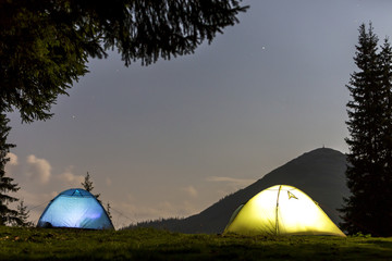 Two brightly lit tourist tents on green grassy forest clearing on dark mountain and clear blue starry sky copy space background. Tourism, night camping in summer mountains, beauty of nature concept.