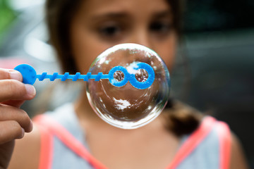 Close up of a girl blowing soap bubble