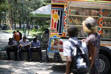Boys read comics next to a Biblio Tap-Tap, a mobile library, in a park of Port-au-Prince