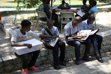 A boy selling pasties looks the book of a student who reads next to a Biblio Tap-Tap, a mobile library, in a park of Port-au-Prince