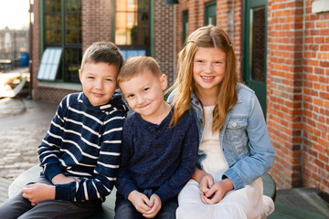 Portrait of smiling siblings sitting outdoors