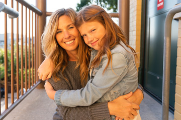 Portrait of smiling mother and daughter sitting on balcony