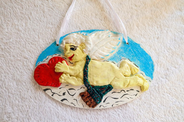 Cupid with a red heart in his hands. Handmade pendant decoration from dough.