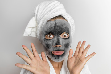 Face mask bubble foam facial funny woman at beauty spa looking shocked or surprised, scary chemicals in beauty products. Asian girl wearing bath towel on hair.