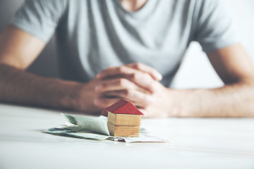 Man  holding a model of a house with money