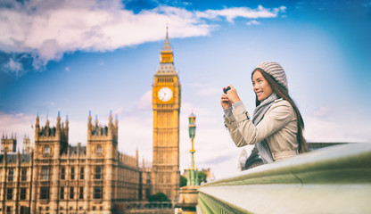 London europe travel woman taking pictures with phone. Mobile photography. Tourist holding smartphone camera taking photos at Big Ben, Westminster Bridge, London, England. British people.