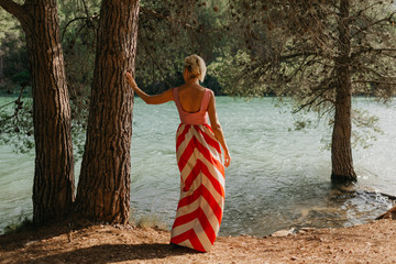 A stylish attractive blonde woman in the red and white dress posing near the old tree near the mountain lake. Portrait from behind. Spain