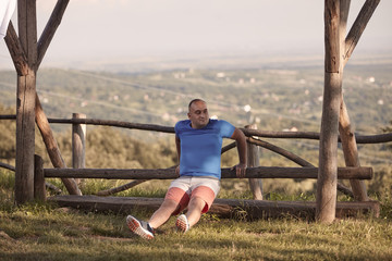 one young overweight man, outdoors, looking sideways. sport clothes, stretching exercise. rural area. 30-35 years, full lenght shot.