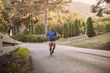 one young overweight man, outdoors nature, running on asphalt road. full length shot, trees, beautiful scenery, vegetation. National park Fruska Gora, Serbia.