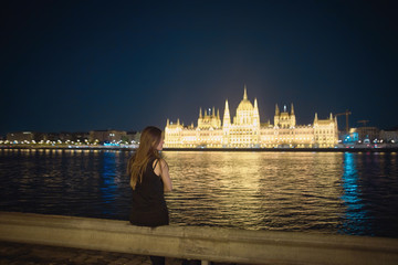 night view of hungary parliament  in budapest with girl in front