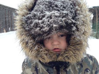 Village boy in frosty hat returns to school after winter holidays. Snowy cold winter. Chrismas story.