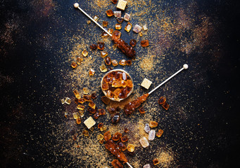 Sweet food background, assorted white and brown sugar on a dark background, top view