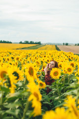 Young beautiful woman in a dress among blooming sunflowers. Agroculture.