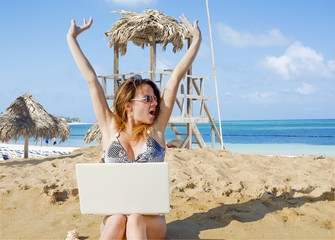 Girl with laptop on tropical beach. remote working concept