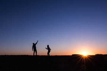 silhouette of man and woman at sunset dancing