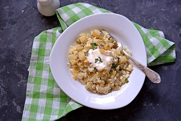 American potato salad with eggs and marinated cucumber on a dark gray background. Served with dressing from mayonnaise and mustard. Top view.