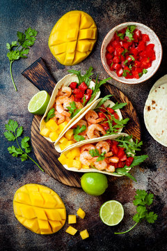 Mexican shrimp tacos with avocado, tomato, mango salsa on rustic stone table. Recipe for Cinco de Mayo party. Top view, overhead, flat lay.