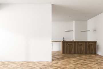 White kitchen interior with bar, blank wall