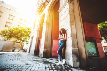 A svelte young charming caucasian female with beautiful curly hair is leaning against the arch column on the street and typing a message to her friend using the smartphone, sunny day in Barcelona