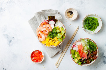 Hawaiian tuna and shrimp poke bowls with seaweed, avocado, mango, pickled ginger, sesame seeds. Top view, overhead, flat lay, copy space