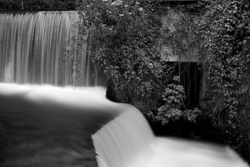 Black and white photo of the waterfall at the mill in Cheddar village in Somerset