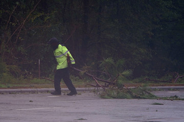 A law enforcement official pulls tree limbs off the road as Hurricane Florence comes ashore in Wilmington