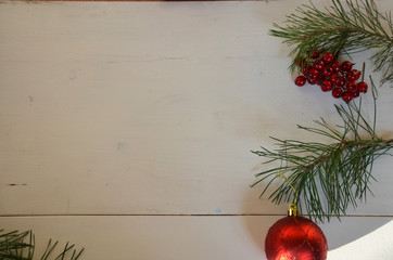 Christmas background with decorations and gift boxes on white wooden board. red ball, gift tied with white ribbon
