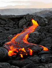 "A lava flow emerges from an earth column and flows in a black volcanic landscape, in the sky shows the first daylight - Location: Hawaii, Big Island, volcano ""Kilauea"""