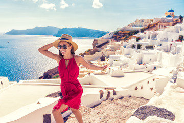 Wall Mural - Europe travel fun - woman tourist running of joy in Santorini city luxury holiday destination. Cruise in Greece for summer holidays. Asian girl in red dress and hat with greek white houses background.