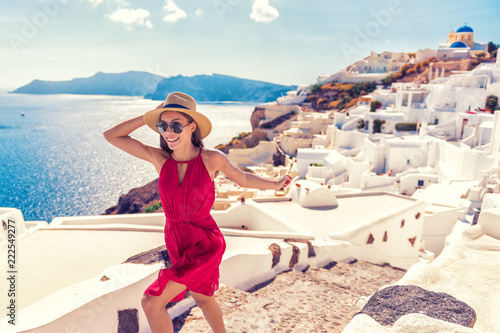 Wall mural Europe travel fun - woman tourist running of joy in Santorini city luxury holiday destination. Cruise in Greece for summer holidays. Asian girl in red dress and hat with greek white houses background.