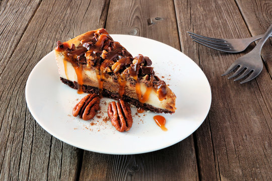 Slice of pecan caramel cheesecake with a rustic wood background. Delicious autumn dessert.