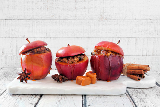 Baked apples with caramel, brown sugar and and nuts. Serving board on a white wood background. Homemade autumn dessert.