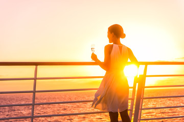 Luxury cruise ship travel elegant woman drinking glass of champagne enjoying watching sunset from boat deck over ocean in Europe destination vacation. Cruising sailing away on holiday.