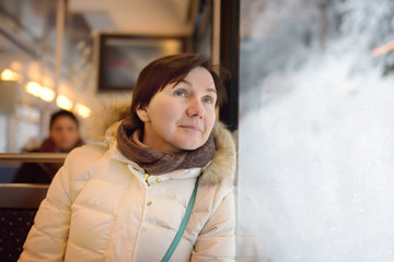 Woman looking out of the window of train during travel on cogwheel railway/rack railway in Alps mountains