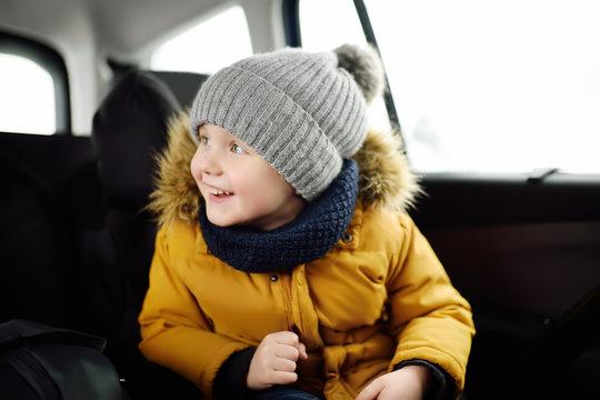 Portrait of pretty little boy sitting in car seat during roadtrip or travel