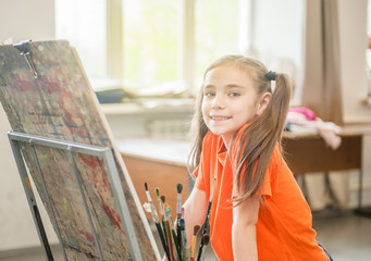 Portrait of a little girl is drawing a picture on easel